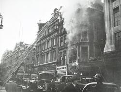 Fire being extinguished by the L C C London Fire Brigade