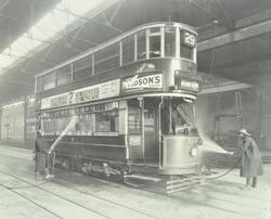 Holloway Car Shed: tram is washed by two men.