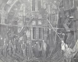Blackwall Tunnel: a group of workers stand in the air lock.